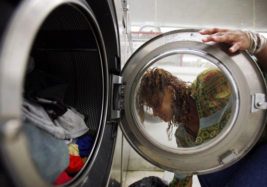 A woman loads laundry into the washing machine at a laundromat in Cambridge, Massachusetts July 2009