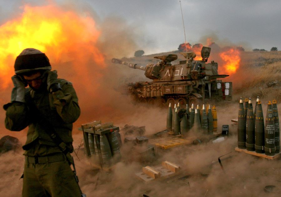 An Israeli soldier stands near a mobile artillery unit as it fires a shell into Lebanon, July 2016.