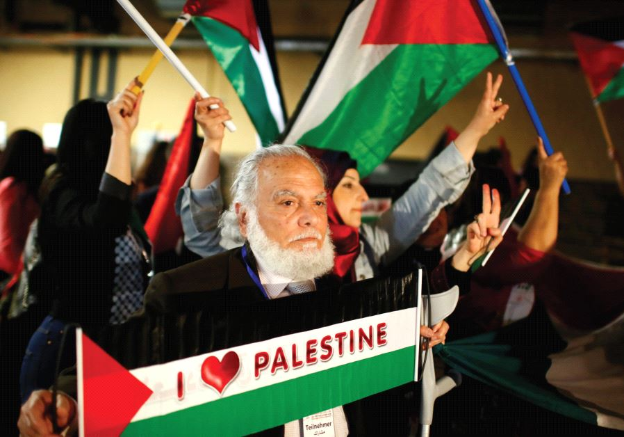 PEOPLE HOLD Palestinian flags during the Conference of Palestinians in Berlin in 2015.