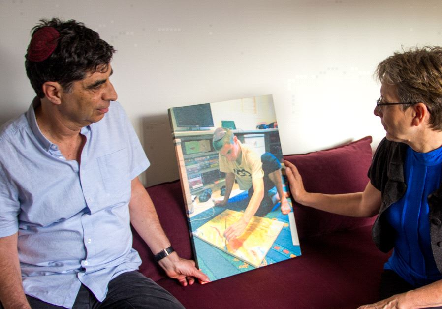 Simha and Leah Goldin with a   photo of Hadar doing one of the activities he loved - painting - his