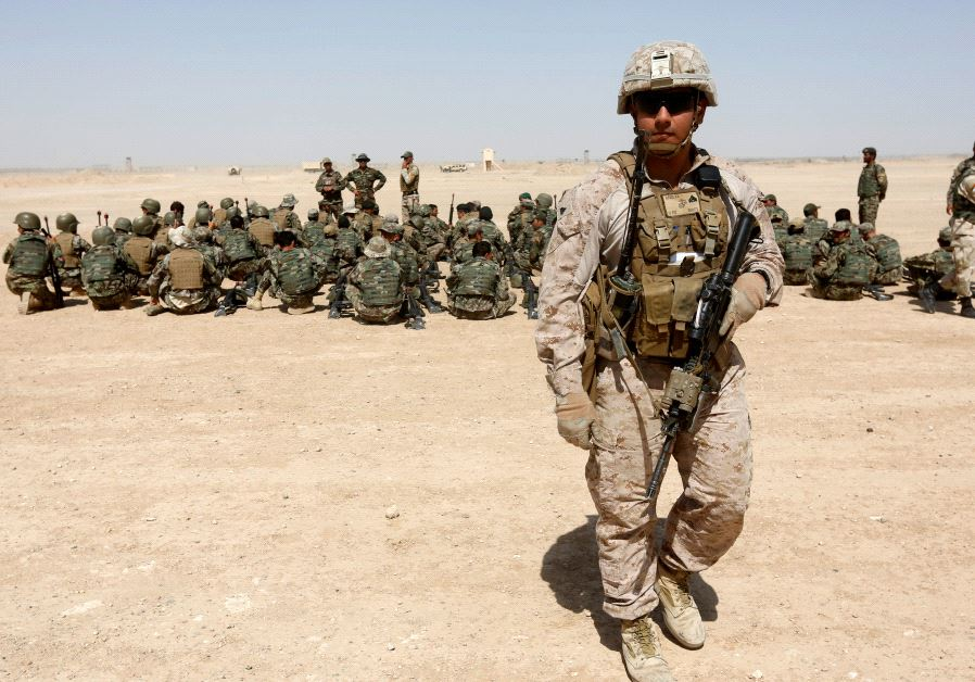 A US Marine walks near Afghan National Army (ANA) soldiers during training in Helmand province.