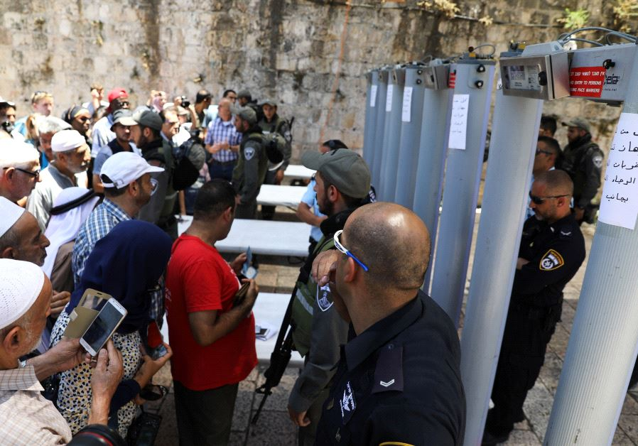Palestinians stand in front of Israeli police officers at Temple Mount.