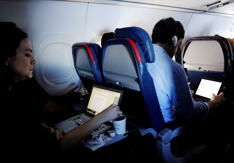 Passengers use their laptops on a flight out of John F. Kennedy (JFK) International Airport in New Y