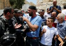 A Palestinian argues with an Israeli border police officer during scuffles that erupted after Palest