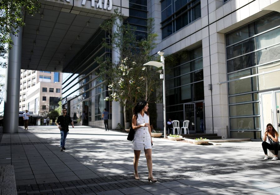 A woman walks near high-rise buildings in the hi-tech business area of Tel Aviv (photo credit: REUTERS/AMIR COHEN)