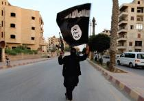 A MEMBER of ISIS waves the group's flag in Raqqa recently