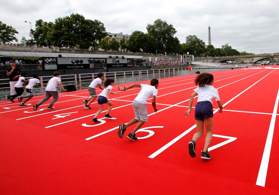 Children take the start in a 100m race on an athletics track installed on the River Seine in Paris,