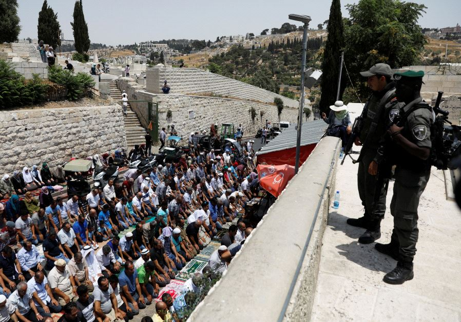Israeli border police officers stand guard as Palestinians pray at Lions' Gate, the entrance to Jeru
