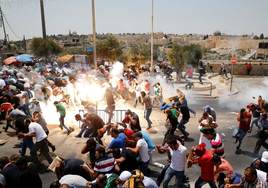 Palestinians react following tear gas that was shot by Israeli forces after Friday prayer on a stree