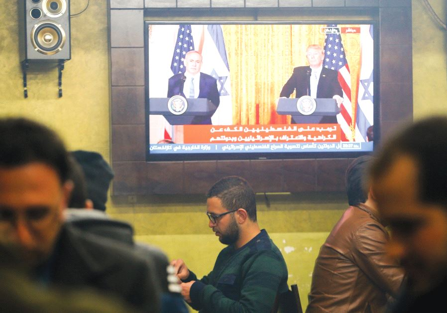PALESTINIANS GATHER in a coffee ship in Hebron, where a TV screen shows US President Donald Trump an