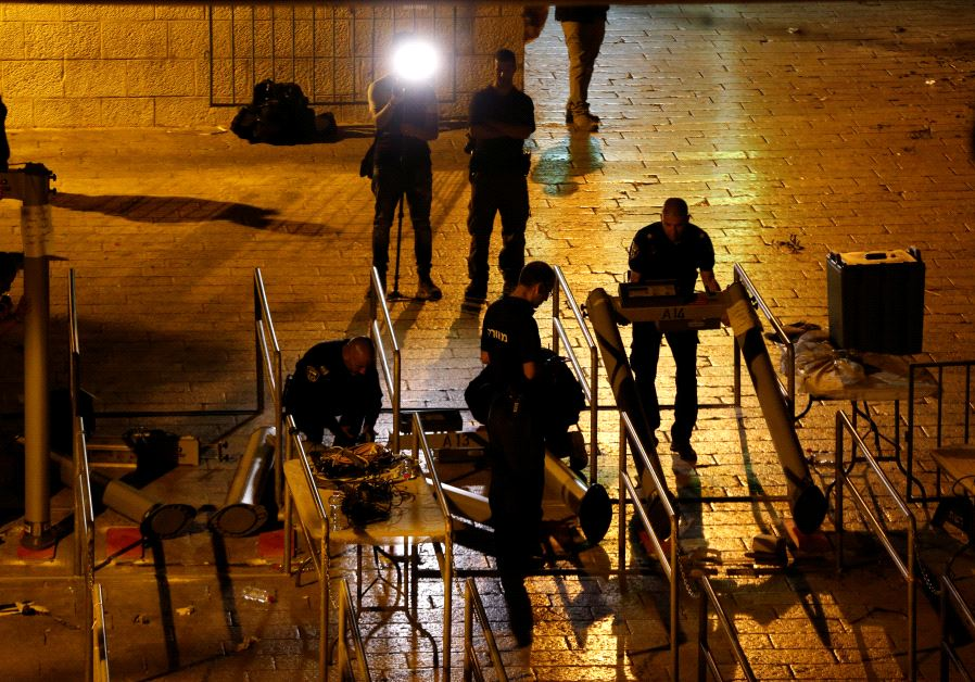 Israeli security forces remove metal detectors which were recently installed at an entrance to the T