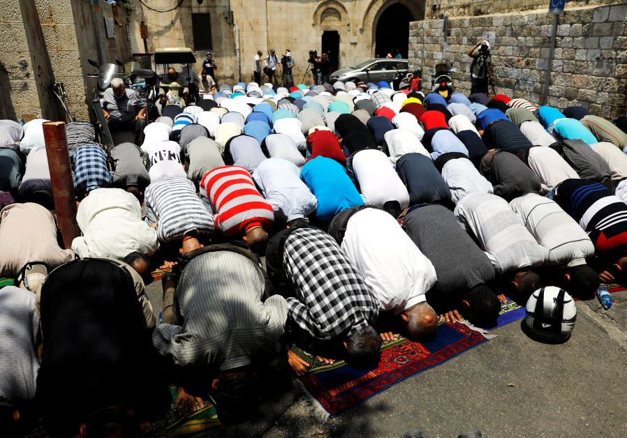 Palestinian men pray outside the Temple Mount after Israel removed the new security measures there,
