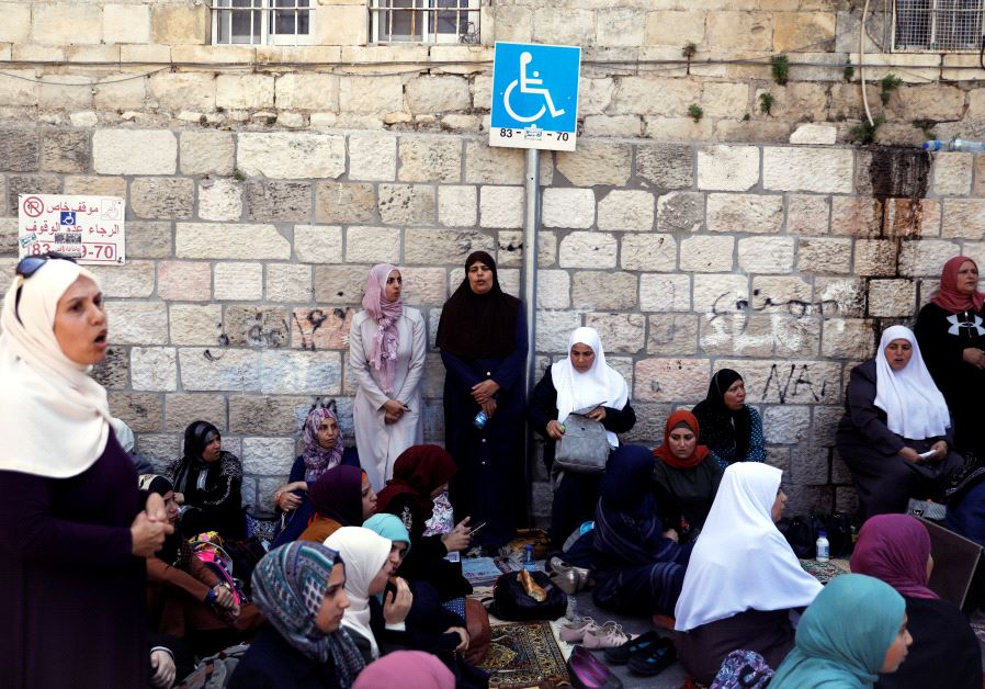 Palestinian women shout slogans as they sit outside the Temple Mount at morning after Israel removed the new security measures there, in Jerusalem's Old City July 25, 2017. (Reuters)