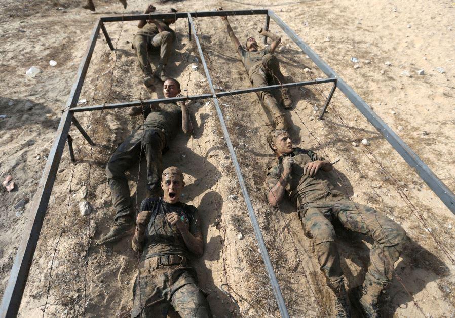 Los jóvenes palestinos se arrastran bajo un obstáculo durante un ejercicio de estilo militar en un campamento de verano de Hamas i