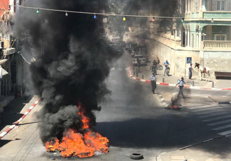 Protestors burn tires during clashes with police in Jaffa, July 29, 2017.