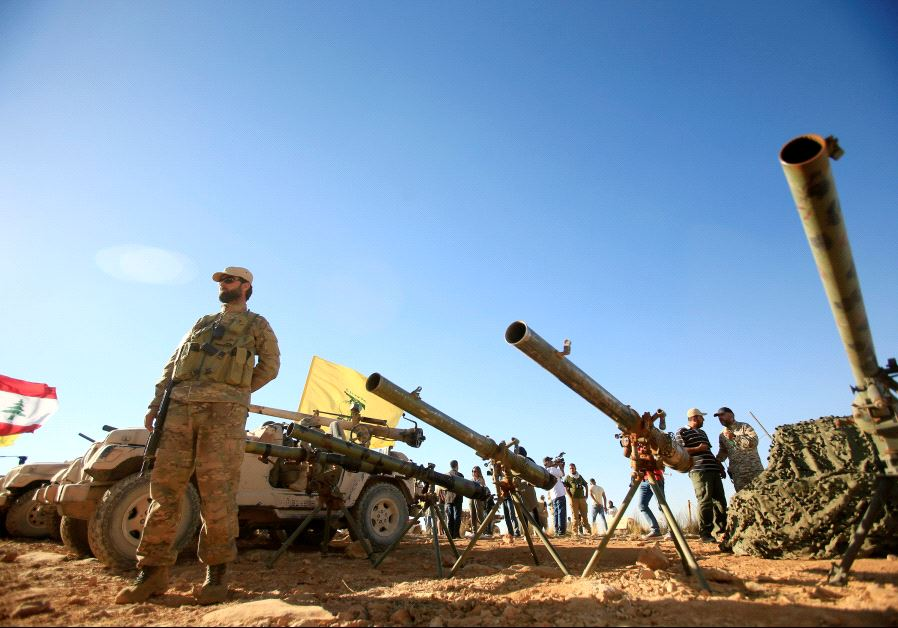 A Hezbollah fighter stands in front of anti-tank artillery at Juroud Arsal