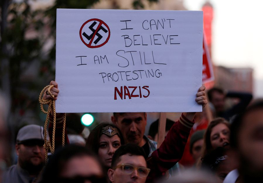 A demonstrator holds signs during a rally in response to the Charlottesville, Virginia nazi