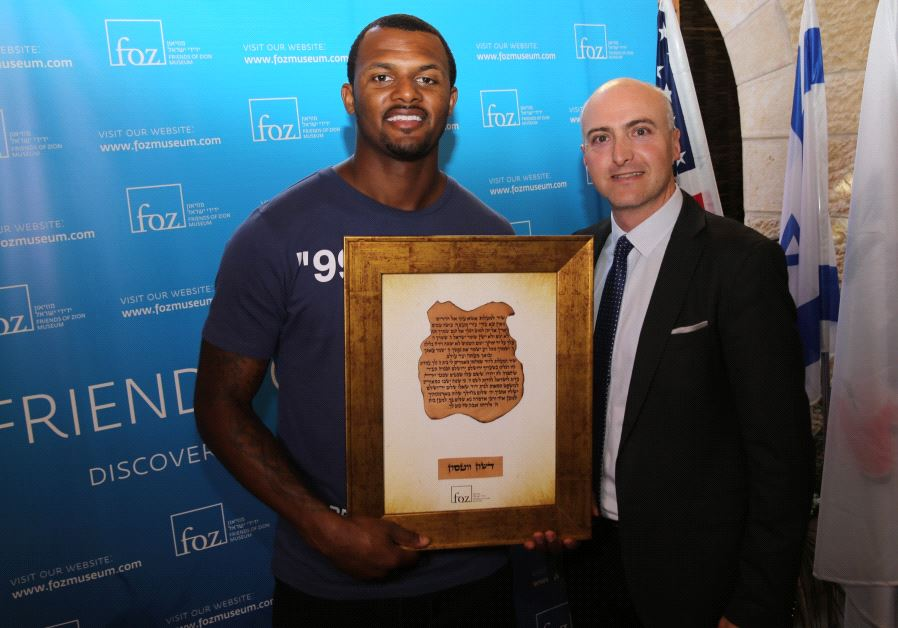 NFL Pro-Bowl quarterback Deshaun Watson receives an award from Friends of Zion Museum's Ilan Scolnik