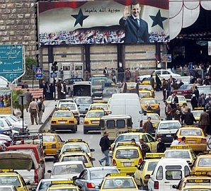 poster of assad over damascus boulevard