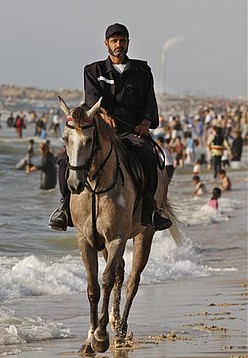 A Mounted Hamas security officer patrols the beach